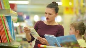 微笑的母亲和女儿超级市场的 女儿帮助她的母亲选择书 Cutie在a的女儿开会 股票视频