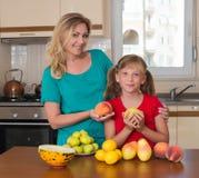 微笑的母亲和她保持的甜梨女儿 健康吃-妇女和孩子在用不同的种类的厨房里果子 图库摄影