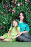 微笑的母亲和小女儿坐草在庭院里 免版税库存图片