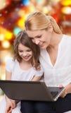 微笑的母亲和小女孩有膝上型计算机的 库存图片