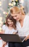 微笑的母亲和小女孩有膝上型计算机的 免版税图库摄影