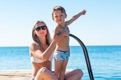 年轻微笑的母亲和播放在天时间的男婴儿子海滩 库存照片