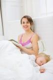 微笑的母亲阅读书,当婴孩休眠时 免版税库存照片