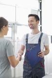 微笑的汽车修理工与汽车维修车间的女性顾客握手 库存图片