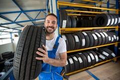 微笑的汽车机械师运载的轮胎 图库摄影