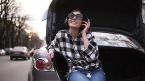 微笑的浅黑肤色的男人听到在耳机的音乐,当坐在路中时的开放汽车` s树干 按移动电话 好 股票录像