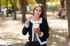 微笑的深色的女孩测试中国鸡蛋noodless在自然背景的公园 库存照片