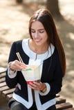 微笑的深色的女孩测试中国鸡蛋noodless在自然背景的公园 免版税库存照片