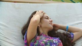 年轻微笑的深色的妇女在热带海滩的吊床放松了 关闭 股票录像
