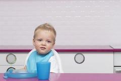 微笑的滑稽的小孩画象蓝色围嘴的在高脚椅子在立即可食现代的厨房里 复制空间 免版税库存图片