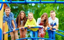 微笑的激动的孩子获得乐趣一起在操场 免版税库存照片