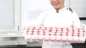 微笑的点心师的播种的射击提供盘子用桃红色蛋白杏仁饼干 股票视频