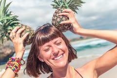 微笑的热带夏天妇女画象用在头的菠萝 巴厘岛 库存照片