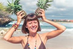 微笑的热带夏天妇女画象用在头的菠萝 巴厘岛 免版税库存照片