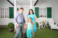 微笑的父亲、母亲和女儿站立近的门廊 免版税图库摄影