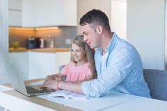 微笑的父亲和一个小女儿在家 库存照片