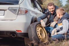 微笑的父亲和儿子改变的汽车 库存图片