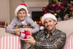 微笑的父亲和儿子画象圣诞节的 库存照片