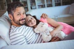 微笑的父亲和女儿坐有玩具熊的沙发 免版税库存图片