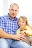 微笑的父亲和女儿有玩具熊的 库存照片