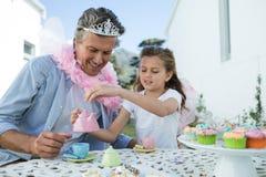 微笑的父亲和女儿有神仙的服装的茶会 免版税图库摄影