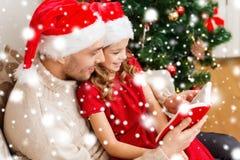微笑的父亲和女儿阅读书 免版税库存图片