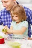 微笑的父亲和小女孩厨房的 免版税库存照片