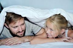 微笑的父亲和获得他的女儿躺在床上的乐趣 库存图片