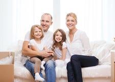 微笑的父母和两个小女孩在新的家 免版税库存照片