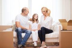 微笑的父母和小女孩在新的家 免版税图库摄影