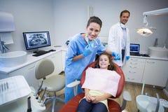 微笑的牙医和年轻患者画象  免版税库存图片