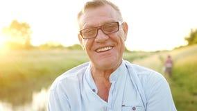 微笑的特写镜头画象,快乐的退休人员 光学玻璃的一个人反对落日、领域和河 影视素材