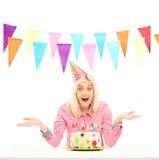 微笑的生日女性佩带的党帽子和打手势 免版税库存图片