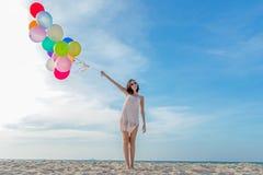 微笑的生活方式亚裔妇女递拿着在海滩的气球 在暑假放松并且享用 免版税库存图片