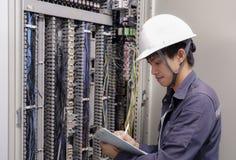 微笑的电工,检查电子箱子在工业工厂 免版税图库摄影
