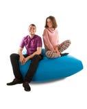 年轻微笑的男人和妇女坐蓝色装豆子小布袋沙发孤立 免版税库存图片
