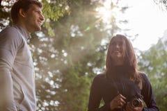 微笑的男人和妇女摄影师在有太阳火光的森林森林点燃 小组朋友人夏天冒险 库存照片