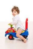 微笑的男孩乘坐一个大汽车玩具 库存照片