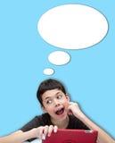 年轻微笑的男孩单手基于与讲话泡影的面颊的反对蓝色背景 图库摄影