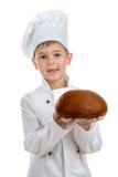微笑的男孩厨师拿着可口新鲜面包,隔绝在白色背景 免版税库存照片