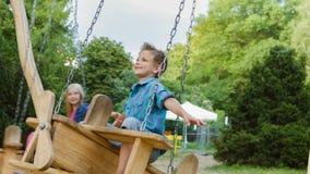 微笑的男孩和女孩获得乐趣在操场 使用户外在夏天的孩子 乘坐在摇摆的少年外面 影视素材
