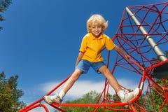 微笑的男孩在与腿的红色绳索分开站立 免版税库存照片
