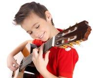微笑的男孩在声学吉他使用 免版税图库摄影