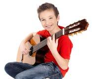 微笑的男孩在声学吉他使用 免版税库存图片