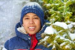 微笑的男孩在有雪的森林剥落 库存照片
