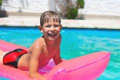 微笑的男孩在桃红色床垫说谎 免版税图库摄影