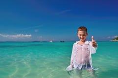 微笑的男孩在清楚的绿松石的10岁立场浇灌美丽的热带海并且显示赞许 概念休息拷贝空间 免版税库存图片