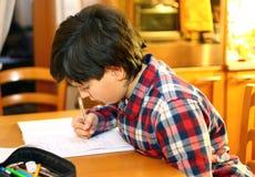 微笑的男孩在他的笔记本写 库存照片