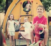 微笑的男孩坐在儿童` s操场的摇摆 图库摄影