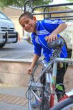 微笑的男孩定象在城市街道,伊朗的边路骑自行车 免版税库存照片